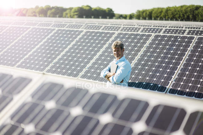 Mature man with laptop standing in solar plant — Stock Photo