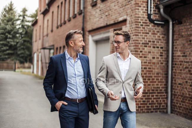 Two businessmen talking at brick building — Stock Photo
