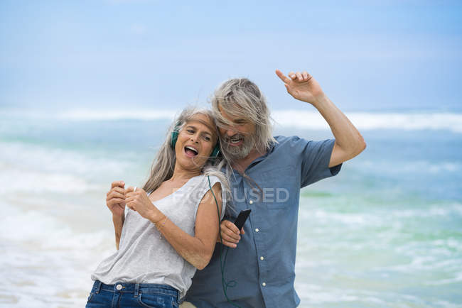 Handsome senior couple with headphones dancing on the beach — Stock Photo