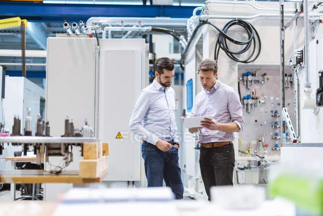 Двое мужчин на фабрике смотрят на планшет — стоковое фото