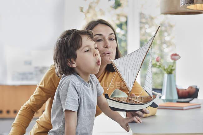 Щасливий мати і син грає з моделлю човен будинку — стокове фото