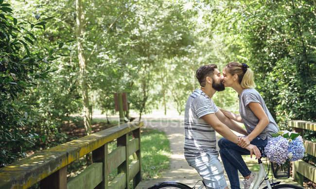 Paar küsst sich mit Fahrrad auf Holzsteg in der Natur — Stockfoto