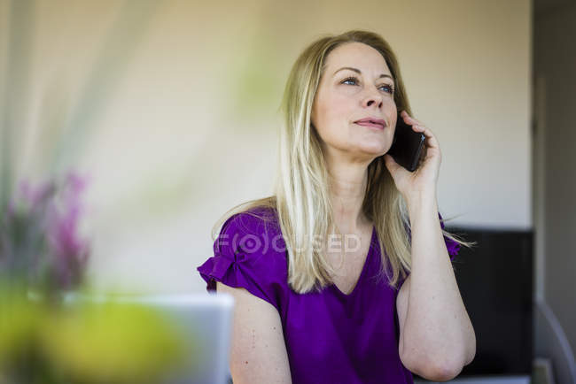 Portrait of blond mature woman  on the phone — Stock Photo