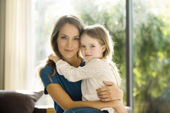 Портрет усміхнена мати тримає дочку будинку — стокове фото