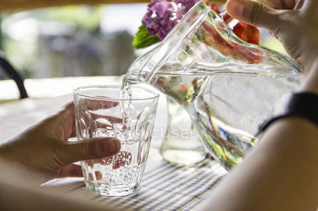 Las manos de la mujer vertiendo agua en el vidrio, primer plano - foto de stock