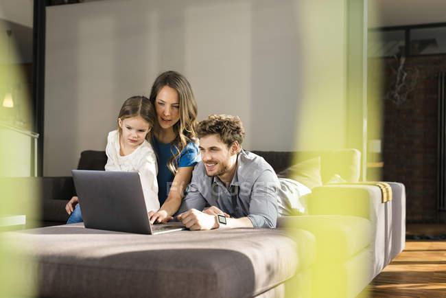 Семья с помощью ноутбука на диване дома — стоковое фото