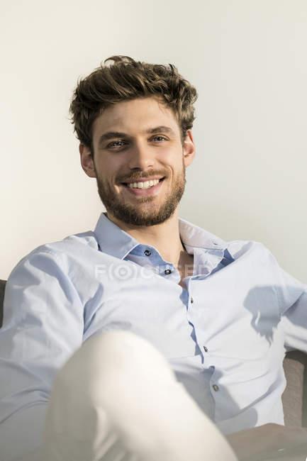 Porträt eines lächelnden jungen Mannes auf der Couch — Stockfoto