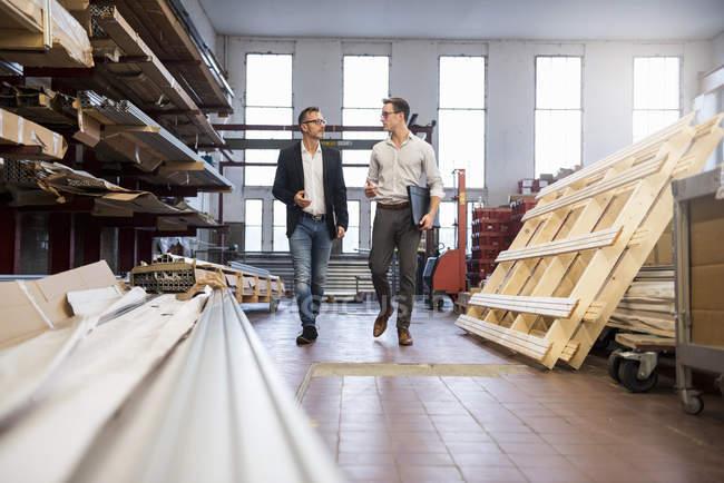 Deux hommes d'affaires marchant et parlant dans la réserve d'usine — Photo de stock