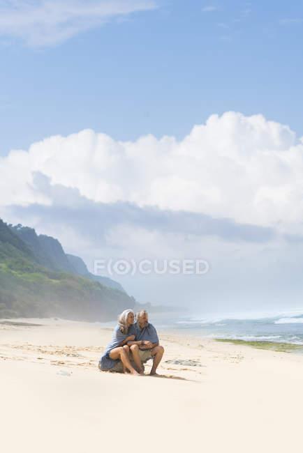 Старша пара сидить на пляжі, загорнутий в ковдру — стокове фото