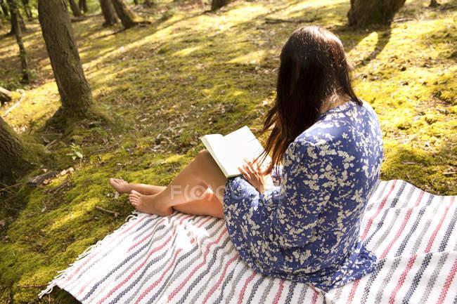 Jeune femme assise sur une couverture en forêt lisant un livre — Photo de stock