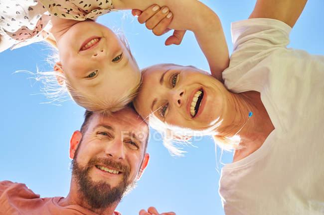 Retrato de família feliz aconchegante sob o céu azul — Fotografia de Stock