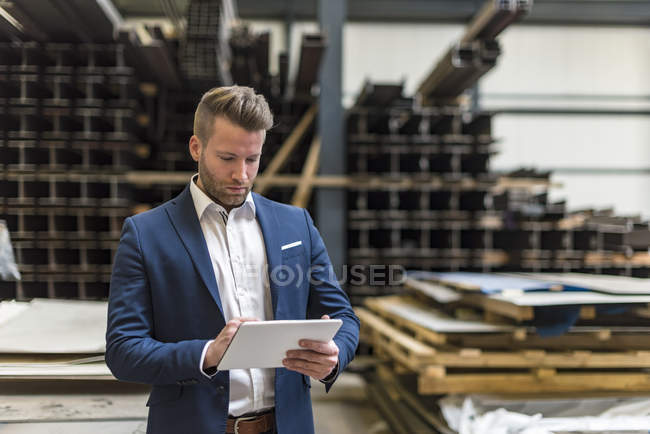 Homme d'affaires avec tablette debout sur le plancher de l'atelier de l'usine — Photo de stock