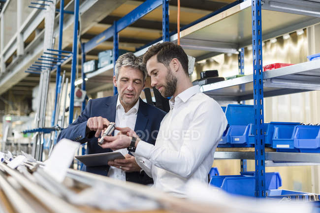 Businessmen during meeting with tablet and product in production hall — Stock Photo