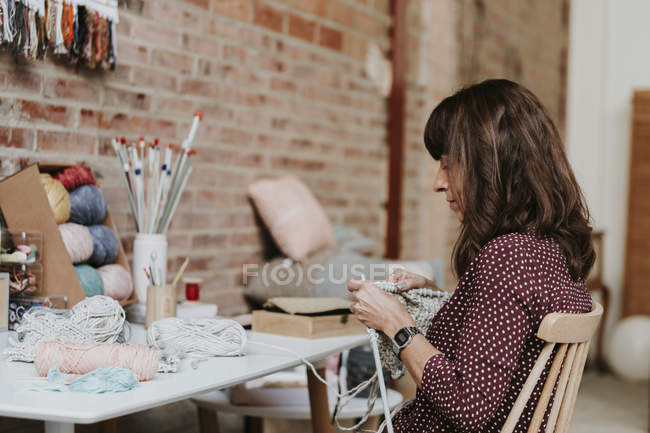 Focused woman knitting at table in room — Stock Photo