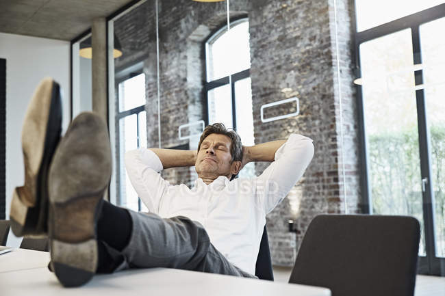 Mature businessman relaxing in conference room of modern office — Stock Photo