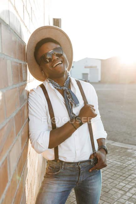 Портрет смеющегося молодого человека в шляпе и солнцезащитных очках — стоковое фото