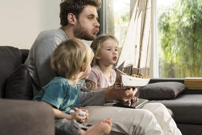 Батько і діти дме на вітрилах іграшки модель корабля на дивані будинку — стокове фото