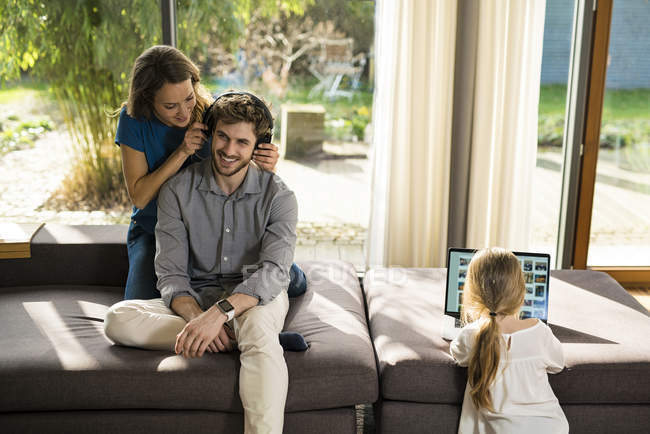 Couple with heaphones and daughter with laptop on sofa at home — Stock Photo