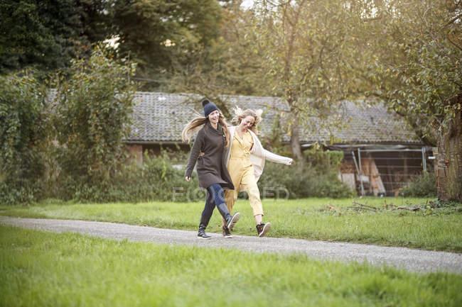 Deux femmes heureuses marchant dans un paysage rural — Photo de stock