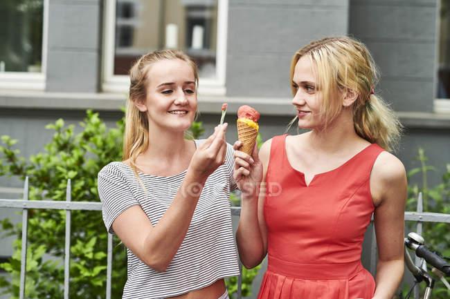 Дві молоді жінки поділяють морозиво в місті. — стокове фото