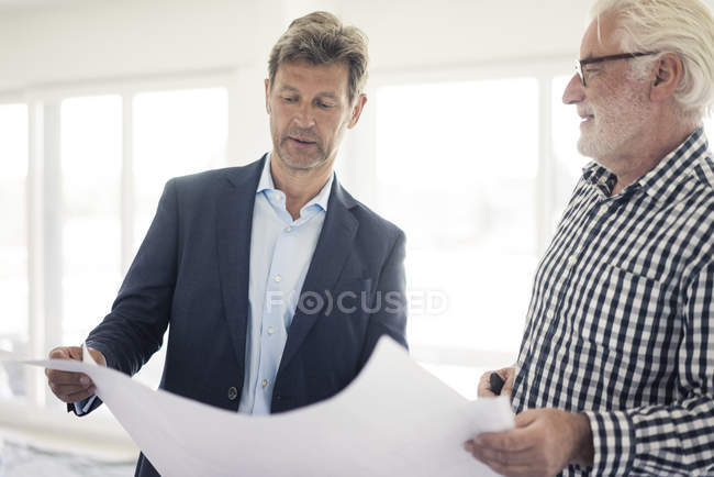 Man in suit and senior man looking at blueprint (en anglais seulement) — Photo de stock