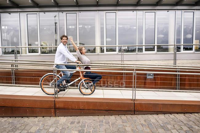 Беззаботная пара на велосипеде в городе — стоковое фото