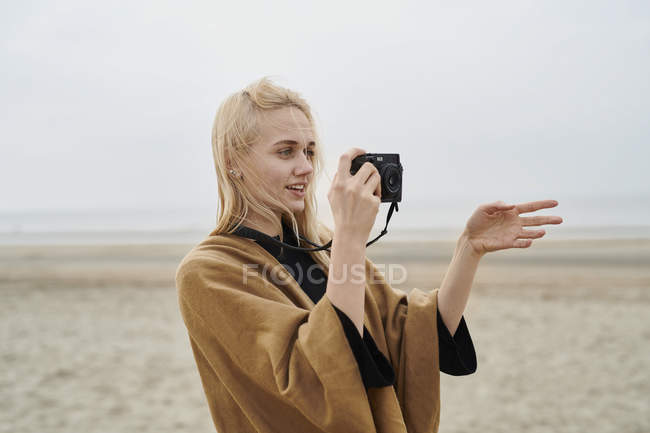 Netherlands, portrait of blond young woman with camera on the beach — Stock Photo