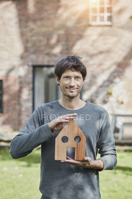 Portrait of smiling man in front of his home holding house model — Stock Photo