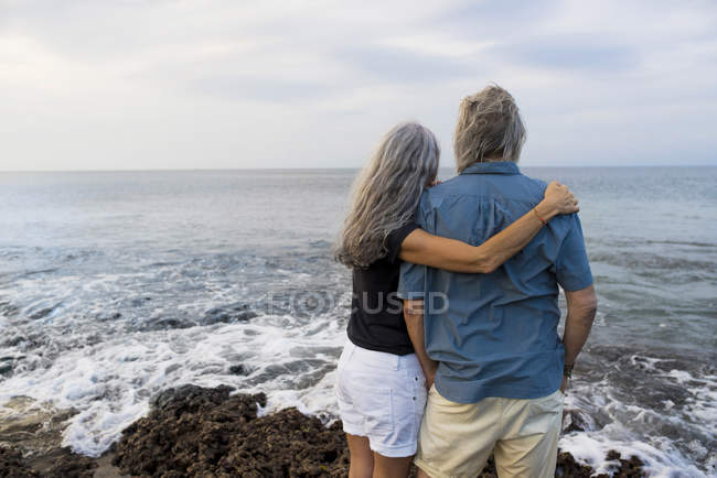 Senior couple looking at the ocean, rear view — Stock Photo
