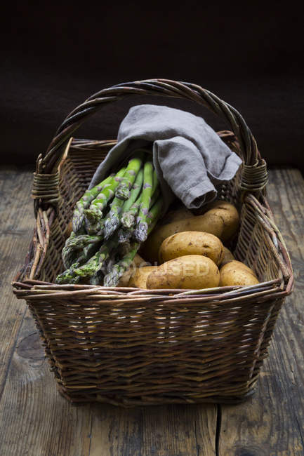 Organic green asparagus and organic potatoes in wickerbasket — Foto stock