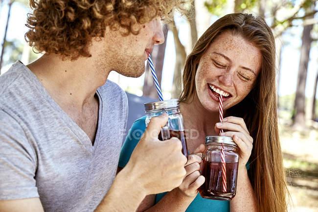 Счастливая молодая пара выпивает в лесу — стоковое фото