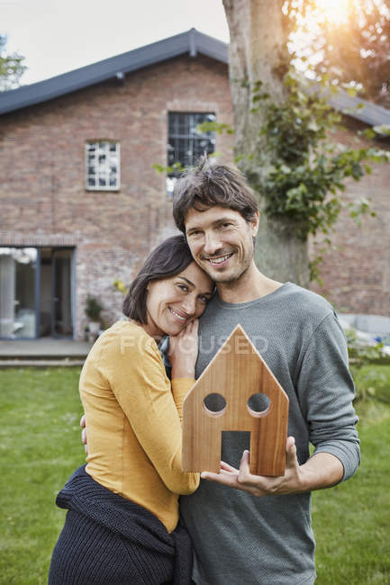 Portrait of smiling couple in garden of their home holding house model - foto de stock