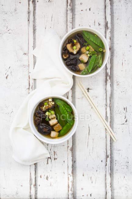 Vue du haut de la soupe japonaise de miso avec des pois de sucre, le shiitake, le tofu et les germes de mung sur la surface en bois — Photo de stock