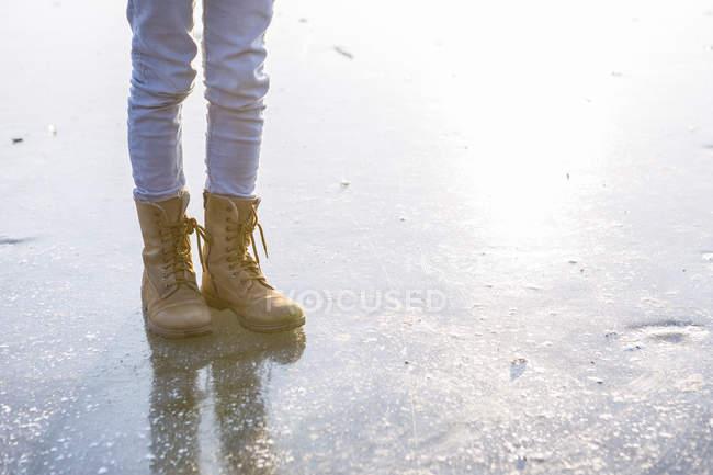 Alemanha, Brandemburgo, Lago Straussee, pés com botas em lago congelado — Fotografia de Stock