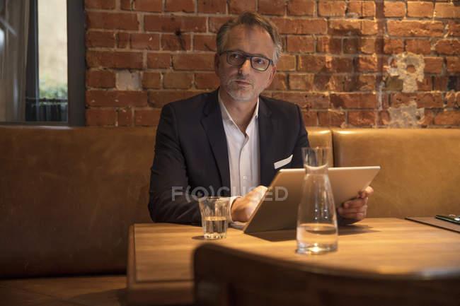 Porträt eines nachdenklichen Geschäftsmannes mit Tablet im Restaurant — Stockfoto