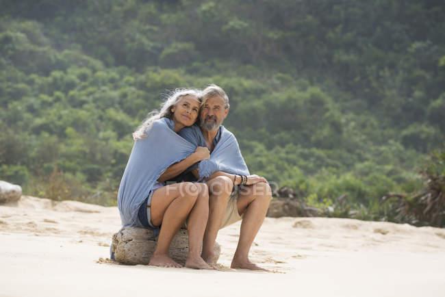 Casal sênior sentado na praia, envolto em um cobertor — Fotografia de Stock