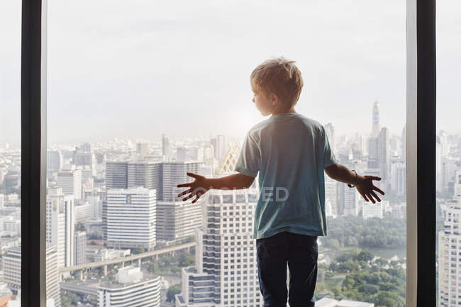 Thailand, Bangkok, boy looking through window at cityscape — Stock Photo