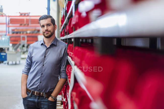 Portrait of man leaning against shelf in storehouse — Stock Photo
