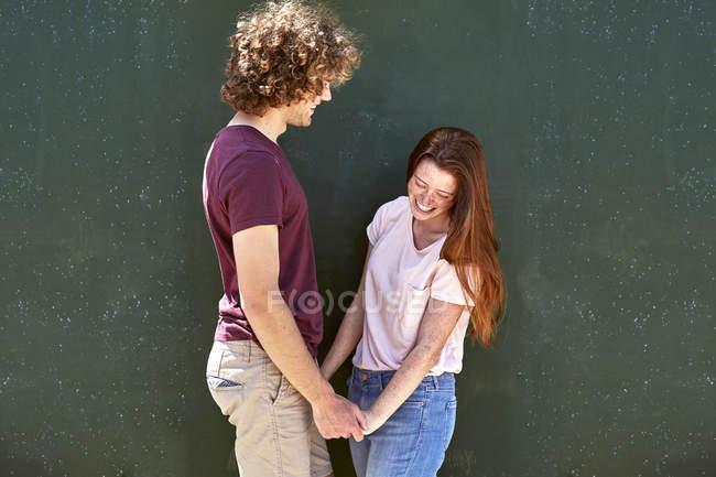 Щаслива молода пара перед зеленою стіною — стокове фото