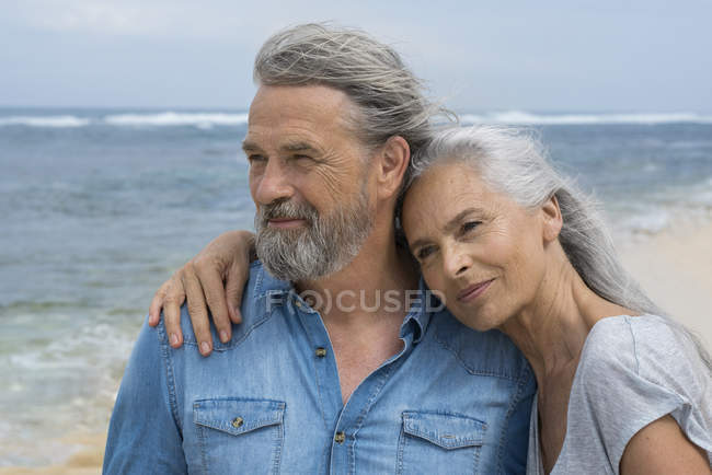 Красивая пожилая пара, обнимающаяся на пляже — стоковое фото
