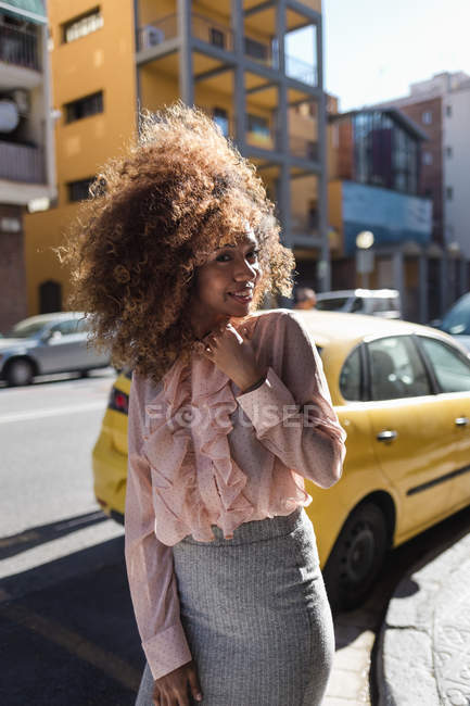 Portrait of smiling beautiful young woman with afro hairdo in the city — Stock Photo