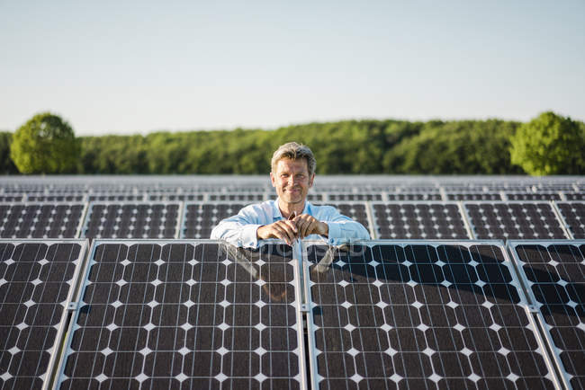 Smailing mature man standing in solar plant — Stock Photo