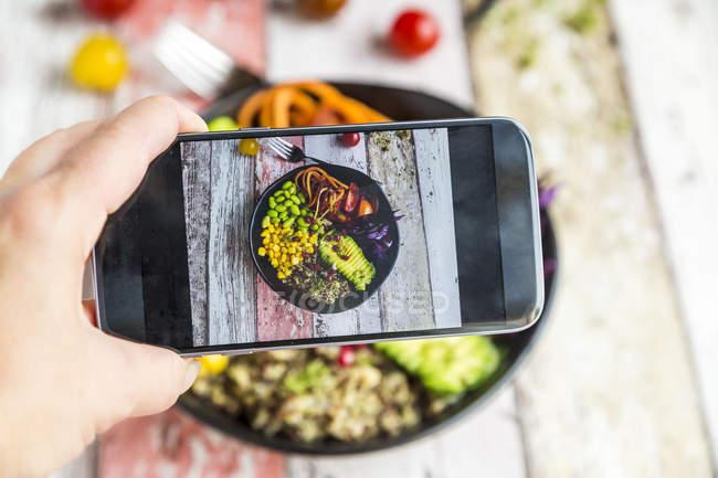 Дівчина беручи фото з вегетаріанець обід чаші з мобільного телефону, Крупний план — стокове фото