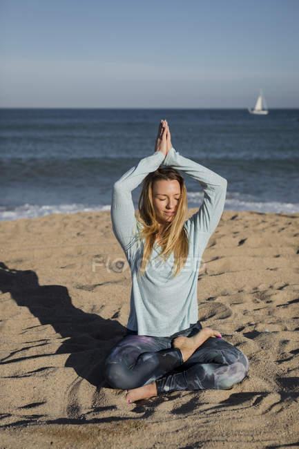 Женщина занимается йогой на пляже, в позе лотоса — стоковое фото