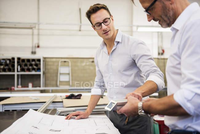 Dos hombres de negocios en la fábrica discutiendo el componente y el plan - foto de stock
