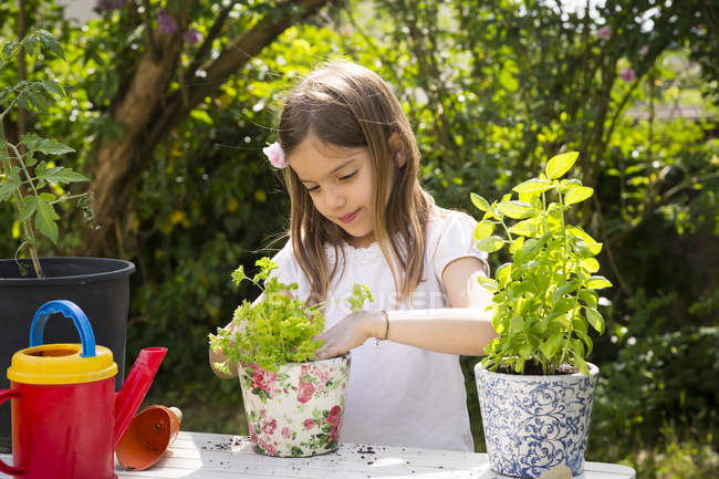 Retrato de menina envasamento salsa na mesa no jardim — Fotografia de Stock