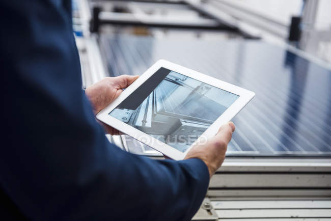 Businessman in solar factory holding tablet — Stock Photo