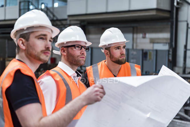 Three men wearing hard hats and safety vests holding plan in factory — Stock Photo