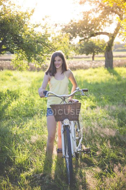 Porträt eines lächelnden Mädchens mit Fahrrad in der Natur — Stockfoto