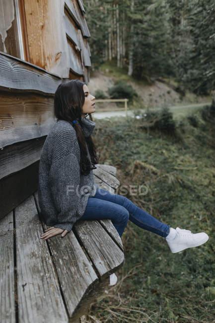 Junge Frau sitzt an einem Holzhaus in der Natur — Stockfoto